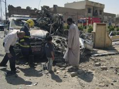 Citizens and security forces inspect the scene of a car bomb attack in Kirkuk, Iraq on Friday.