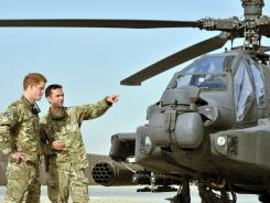 Britain's Prince Harry, left, is shown an Apache helicopter upon his arrival at Camp Bastion in Afghanistan on Friday.