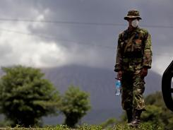 A Nicaraguan soldier wears a protective mask as the San Cristobal volcano spews smoke and ash near Chinandega, Nicaragua, on Saturday.
