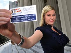 Nikki Goeser shows a card that she hands to restaurant and bar owners asking them not to post signs prohibiting guns on their premises.