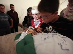 Ten-year-old Mahmoud Azhari, in red shirt, mourns the death of his brother Yousef, 8, during Yousef's funeral on Aug. 22.