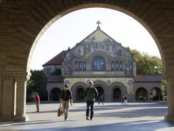 Two students walk in front of Stanford Chapel on the Stanford University campus in Palo Alto, Calif.