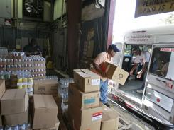 Volunteers load a church bus July 30 with food donated by the Second Haverst Food bank in Orlando, Fla.