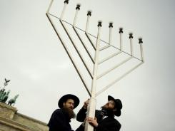 Rabbis Yehuda Teichtal, right, and Shmuel Segal inaugurate the Chanukkah lights in front of Brandenburg Gate in Berlin last December.
