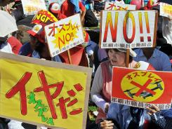 People hold anti-Osprey placards during a rally denouncing the deployment of Osprey military transport aircraft by the U.S. in Japan's Okinawa prefecture on Sunday.