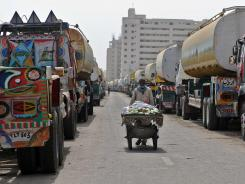 A Pakistani street vendor walks past tanker trucks used to transport fuel to NATO forces in Afghanistan.