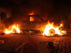A vehicle set on fire burns inside the U.S. consulate compound in Benghazi, Libya, on Tuesday.