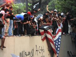 Egyptian protesters tear down the Stars and Stripes at the U.S. Embassy in Cairo on Sept 11.