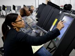 Election workers in Maplewood, Mo., train on touch-screen machines in 2010. Sixteen states use electronic voting devices with no paper backup.