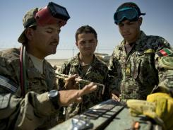 U.S. Army Sgt. Alejandro Villalobos, left, instructs Afghan soldiers on welding techniques Sept. 10 at Camp Hero in Kandahar.
