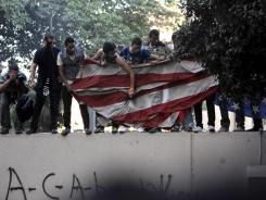 Egyptians remove an American flag at the U.S. Embassy in Cairo.