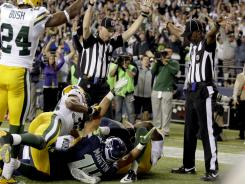 One ref signals touchdown and the other a touchback Monday night at the Seattle vs. Green Bay NFL game.