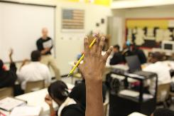 Students raise their hands to answer a question during class at the Knowledge Is Power Program school in Baltimore, Md. Under new U.S. standards, each grade will have fewer goals in each subject area, but each goal goes deeper and some may start to show up earlier than expected. For example, kindergartners are expected to learn to count to 100 and fractions start in third grade.