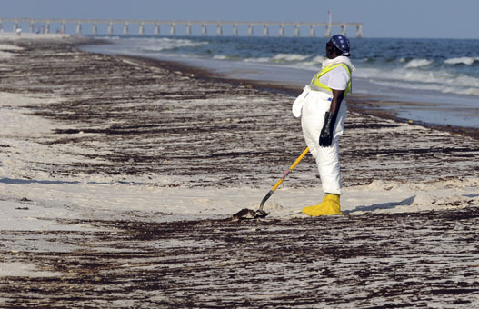 The slow work of collecting oil that's come ashore on Pensacola Beach, Fla.