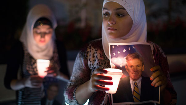 Dilan Samo holds a picture of slain U.S. ambassador to Libya Christopher Stevens during a candlelight vigil outside the Libyan Embassy in New York City. Stevens was killed Sept. 11 during an attack on the U.S. Consulate in Benghazi, Libya, by a mob angered about a film that mocked the prophet Mohammed.Photo By John Minchillo, AP