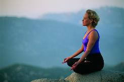 A woman practices yoga and meditation on a mountain near San Diego.