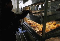 Students get food at a middle school cafeteria in Springfield, Ill., in 2008. To battle the childhood obesity epidemic, many advocates say schools must serve healthier fare.