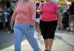 Two women walk at the Montgomery County Agricultural Fair in Gaithersburg, Md. Obesity affects about one-third of U.S. adults.