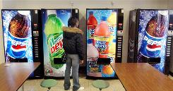 A student debates which beverage to buy at a high school cafeteria in Racine, Wis.