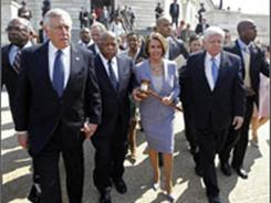 Wielding history: House Speaker Nancy Pelosi, holding the gavel used when the Medicare legislation was passed in 1965, leads fellow Democratic representatives to the health care vote on March 21.