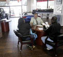 Car salesman Thomas Voik, center, shakes hands with customers Caprice Cannon and Reginald Ross in San Jose, Calif., on Aug. 24.