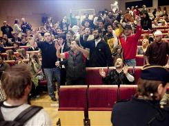 People demonstrate in the room where Swedish artist Lars Vilks was giving a lecture Tuesday at Uppsala University, in Uppsala, Sweden.