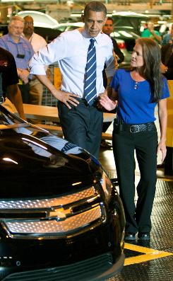 President Obama confers with plant Manager Teri Quigley as a 2011 Chevrolet Volt electric vehicle rolls off the line at the General Motors Detroit-Hamtramck Assembly Plant on Friday in Hamtramck, Mich.