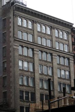"The nine windows on the top story of the Liberty Street building where Russell Simmons lives overlook Ground Zero. The first six windows use the symbols of world religions to spell out ""coexist."""