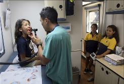 Preventive medical care: Physician Adrian Khaw gives a checkup to Mildred Poyato, while her sisters wait their turn at the University of Miami Pediatric Mobile Clinic. This clinic is for the uninsured.