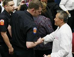 Memorial: Tucson rescuers greet Peter Rhee, head of the surgery team for Gabrielle Giffords.