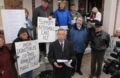 Dr. Don Nguyen, foreground center, of Doctors for America, discusses a petition in support of the health care reform law.