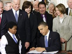 Medical reform: The president signs the health care bill into law in March 2010.