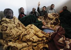 Suspected African mercenaries sit in a jail cell in Benghazi, Libya, on Friday. Anti-Gadhafi forces said they had captured the men.
