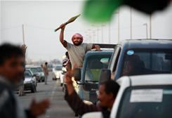 A Libyan rebel from the forces against Moammar Gadhafi holds a rocket propelled grenade round as he and others arrive to help the fight in eastern Libya.