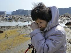A woman cries as she looks for her missing husband in northern Japan on Sunday, two days after a powerful earthquake-triggered tsunami hit the country's east coast.