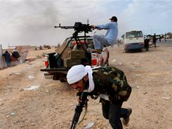Rebels resist: Libyan fighters try to defend the key northern oil town of Ras Lanuf. 