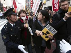 People confront police during an anti-war and anti-nuclear march Sunday in Tokyo.