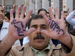"'Yes for freedom': And ""no to violence,"" read the hands of this anti-government protestor in Damascus on Friday, when thousands demonstrated for reforming Syria."