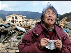 Catastrophe: A woman cries in the devastated town of Rikuzentakata, Japan.