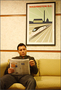 After arriving by Amtrak train, De La Hoya relaxes with a newspaper in a holding room at Washington's Union Station before for a news conference there.