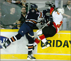 Georges Laraque, left, shown decking Calgary's Toni Lydman in 2003, is a notorious NHL bruiser. Perhaps that is what Pittsburgh had in mind when they acquired him from Phoenix.