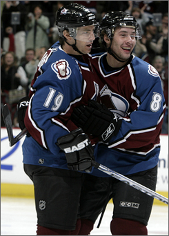 Colorado's Joe Sakic, left, celebrates his first-period goal with teammate Wojtek Wolski. The score moved Sakic into 16th on the NHL all-time list.