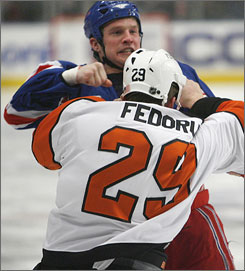 Colton Orr and Todd Fedoruk square off in their first-period bout Wednesday in New York.