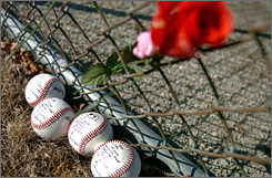 Baseballs enscribed with the names of the killed Bluffton players lie on the ground near the school's diamond. The team  has decided to take the field Friday as part of the healing process.