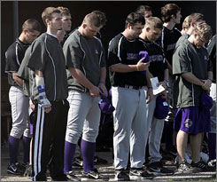 Members of the Bluffton University baseball team pause during a moment of silence to before their first game since five teammates were killed in a bus crash.