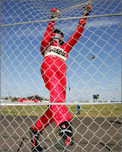 Helio Castroneves performs his trademark celebration with a fence-scaling clinic after his second straight win in St. Pete.