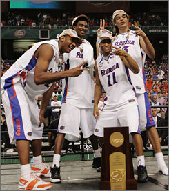 Florida's stellar junior class of (l-r) Al Horford, Corey Brewer, Taurean Green and Joakim Noah celebrate with the trophy after finishing off their quest for a second straight title. Brewer was named the Final Four's Most Outstanding Player after tallying 32 points in two games in Atlanta.