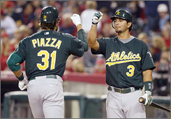 Mike Piazza gets a big hand from teammate Eric Chavez, who cheered what turned out to be a game-deciding home run from Oakland's new DH.