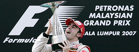 McLaren driver Fernando Alonso celebrates as he holds the Malaysian F1 Grand Prix trophy on Sunday in Sepang.