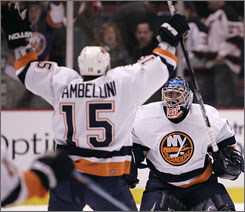 Islanders goalie Wade Dubielewicz celebrates with winger Jeff Tambellini after stopping the final shot in Sunday's playoff-clinching, shootout victory over the Devils.